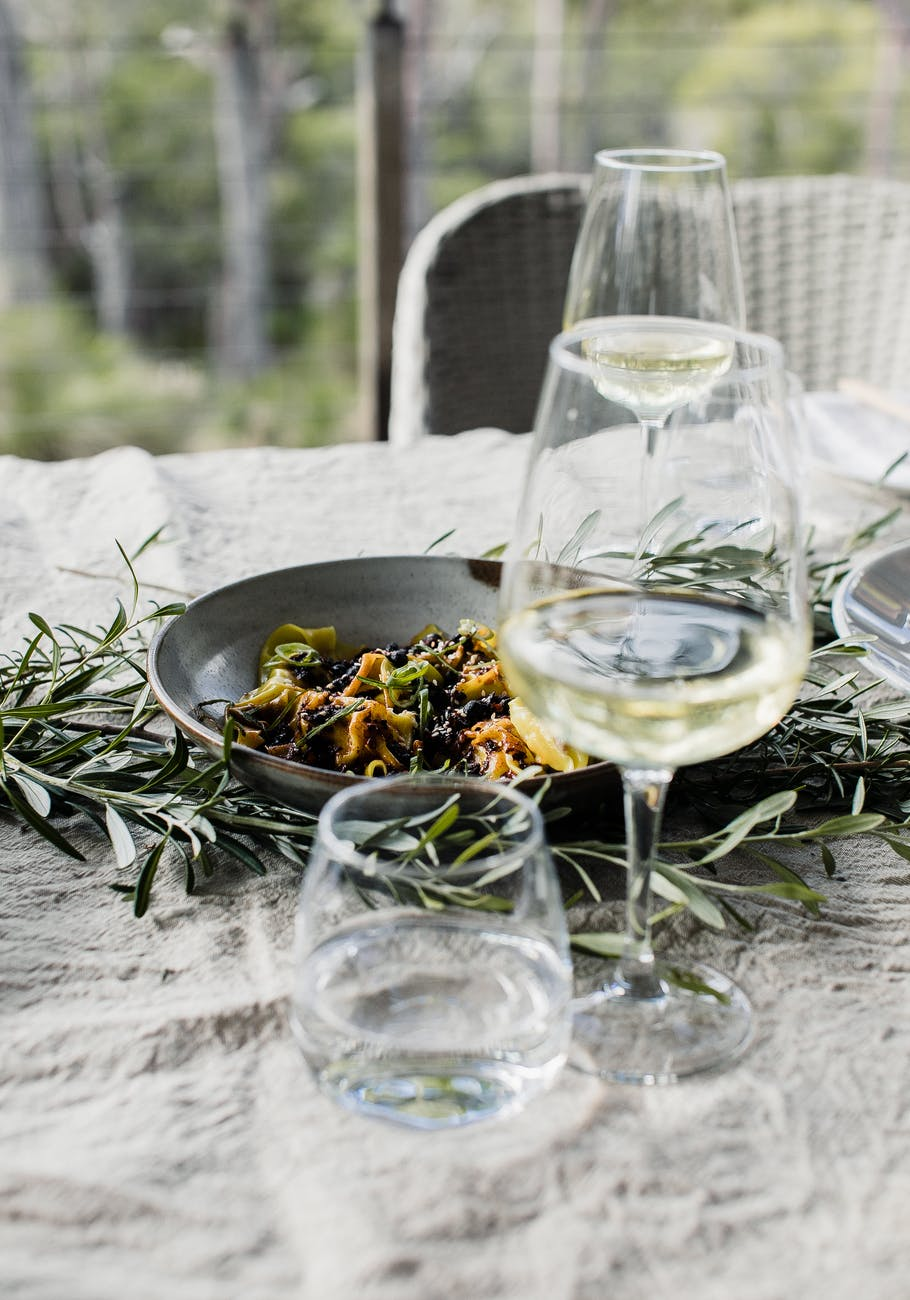 bowl with pasta and wineglasses on table
